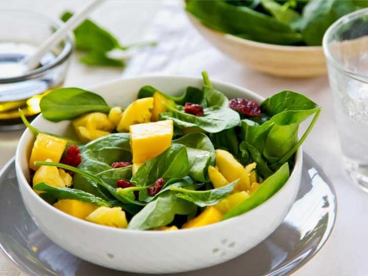 Mango und Ananas an Spinatsalat